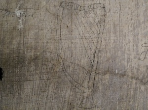 A harp drawn with pencil over whitewash located in a cell on Corridor 2 of the Top Floor with a reference to 'DeValera' referenced within.